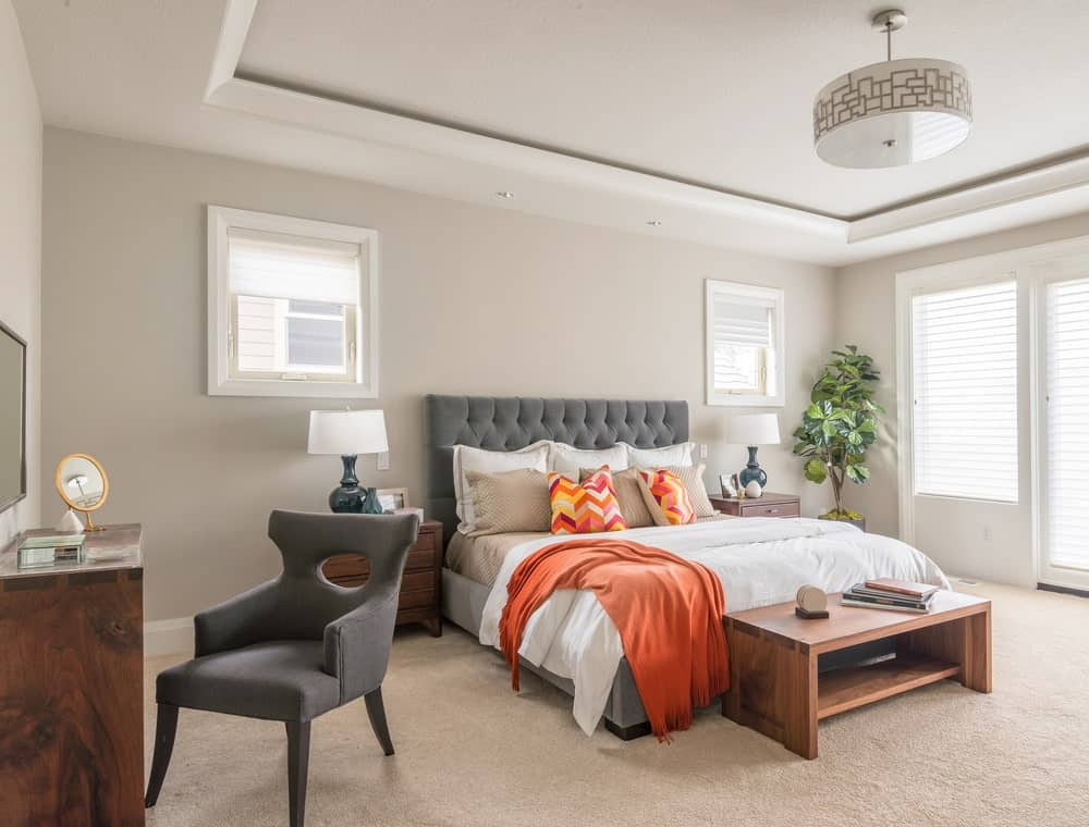 A gray wingback chair matches the tufted bed that's accented with chevron pillows and an orange throw. This primary bedroom showcases beige carpet flooring and a tray ceiling mounted with a stylish drum chandelier.