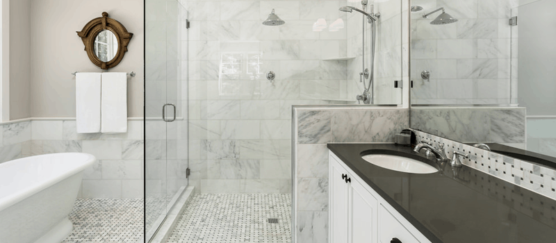 Transitional style primary bathroom with a stylish walk-in shower and a freestanding tub, along with a sink counter with a black countertop.