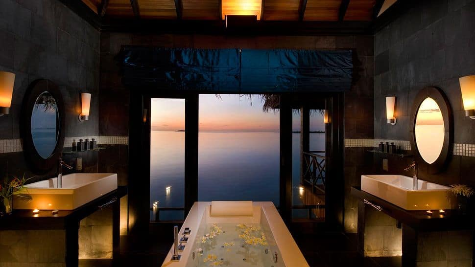 A tropical style primary bathroom with two sink counters with vessel sinks facing each other and lighted by wall sconces, along with a freestanding tub set in the middle. The room also offers a stunning ocean view.