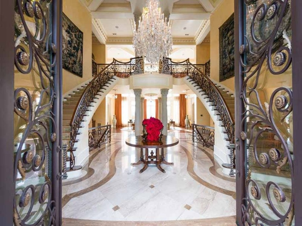 A foyer boasting elegant tiles flooring and a double staircase lighted by a glamorous chandelier.