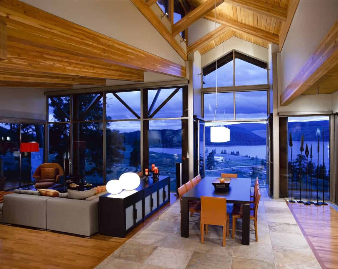 An open concept house with rich hardwood flooring and a high vaulted ceiling accented with exposed wood beams. It is surrounded by tinted full height glazing that overlooks the outdoor scenery.