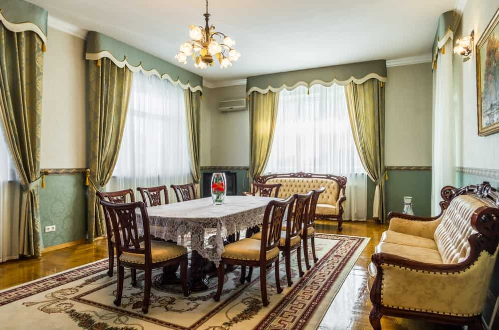 Victorian dining room with polished hardwood flooring and glazed windows dressed in sheer and green draperies. It showcases tufted sofas and a wooden dining set illuminated by a charming chandelier.
