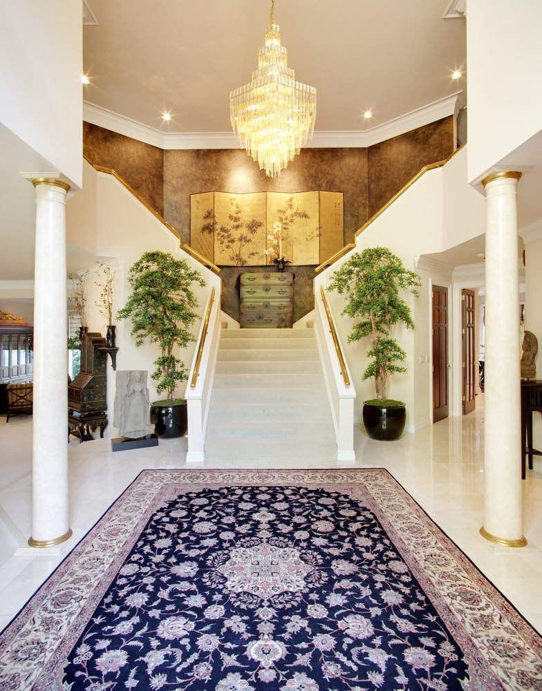Tall potted plants flanked the white staircase that's accented with gold handrails. This foyer features marble columns and a large floral rug illuminated by a cascading crystal chandelier.