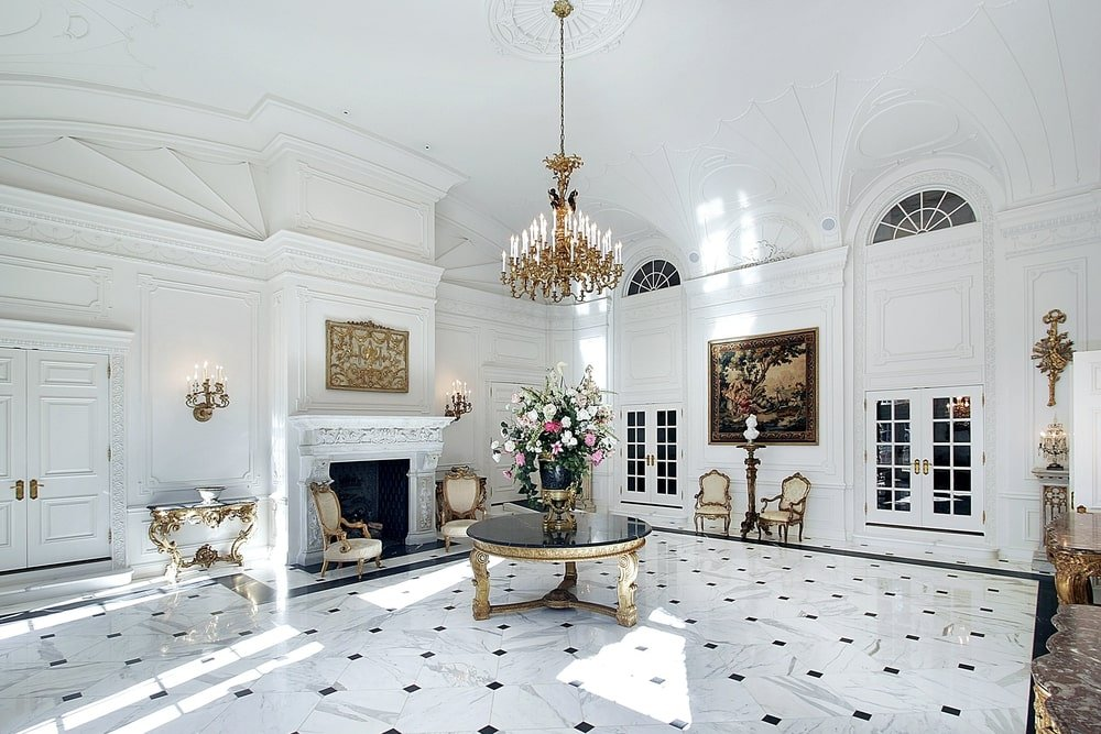 The luxury foyer boasts a grand gilded chandelier hanging over a round center table that's topped with a gorgeous flower vase. It is surrounded by elegant console tables and chairs along with French doors and a fireplace flanked by candle sconces.