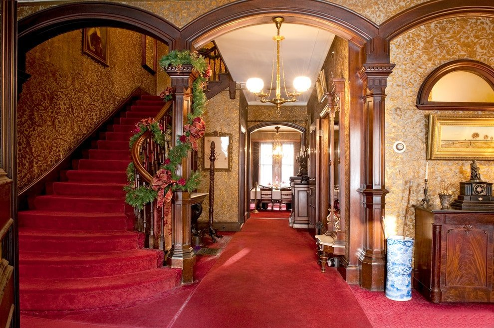 Elegant foyer clad in gold patterned wallpaper and classic red carpet that runs throughout the rooms. It is illuminated by a brass pendant light hanging from the open archway that's wrapped in wooden wainscoting.