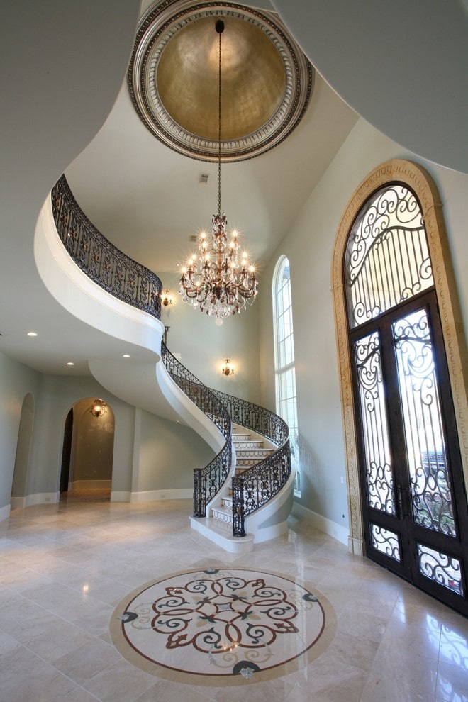 This foyer features a large double front door and a grand candle chandelier that hung from the high ceiling. It is accompanied by a gorgeous winding staircase framed in ornate railings.
