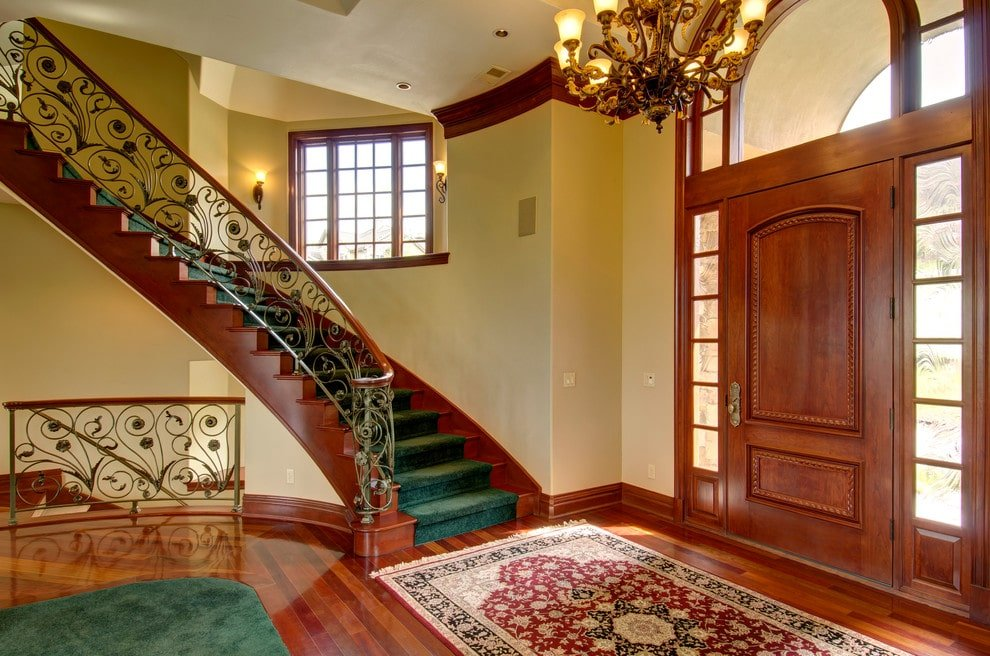 Ornate staircase dressed in green velvet runner adds statement in this classic foyer with warm chandelier and a wooden front door blending in with the polished hardwood flooring topped by green and red printed rugs.