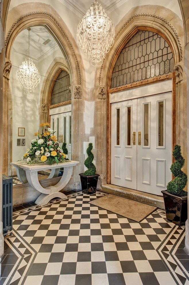 Checkered flooring adds a striking accent in this beige foyer with a concrete console table and a white double entry door complemented by a rug. It is decorated with beautifully manicured plants and a large mirror framed in arched moldings.