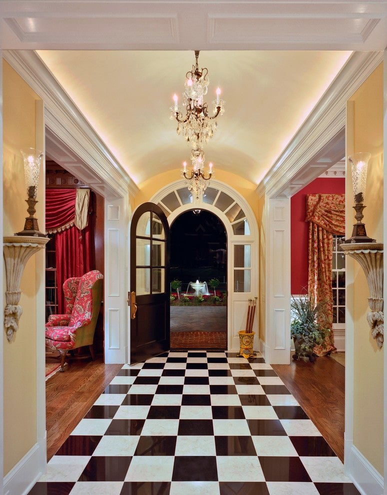 Small foyer flanked by wall sconces and open doorways that are clad in white wainscoting. It has an arched entry door and a striking checkered flooring lit by crystal chandeliers that hung from the barrel vaulted ceiling.