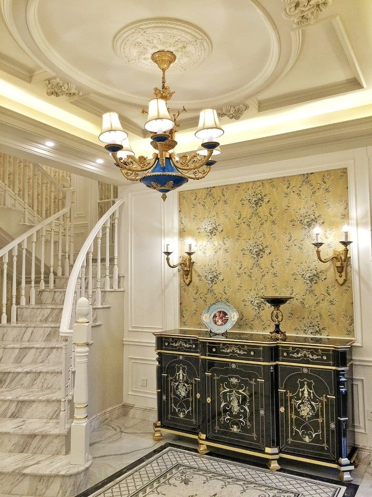 Clad in white wainscoting and yellow floral wallpaper, this foyer offers a classic console table and marble staircase matching with the tiled flooring. It is lighted by candle sconces and a gilded chandelier that hung from the ornate tray ceiling.