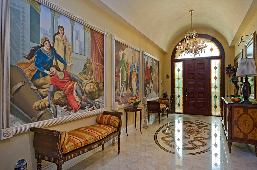 This foyer exhibits large paintings that set a gorgeous backdrop to the dark wood benches with striped cushions and pillows. It has luxurious marble flooring and a barrel vaulted ceiling mounted with a glam crystal chandelier.