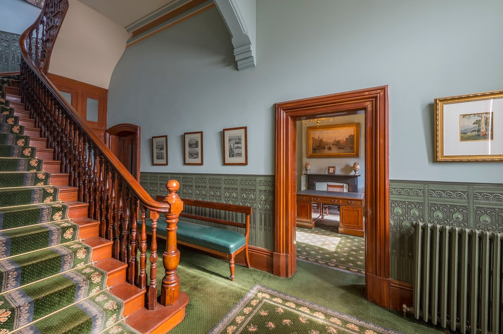 Victorian style foyer filled with framed artworks and a cushioned bench against the textured wallpaper. It has soft blue upper walls and green carpet flooring matching with the runner on a wooden staircase.