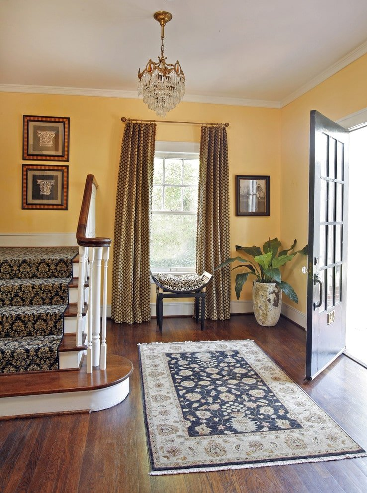 A black front door opens to this foyer with yellow walls and a glazed window dressed in dotted draperies. It features a curved stool and a large floral rug lighted by a cascading crystal chandelier.