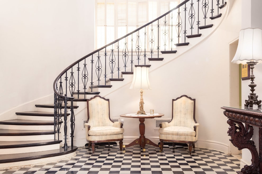 Bright foyer accented with a striking checkered flooring and ornate wrought iron railings fitted on a curved staircase. It is furnished with patterned upholstered chairs and a round side table topped with a stylish lamp.