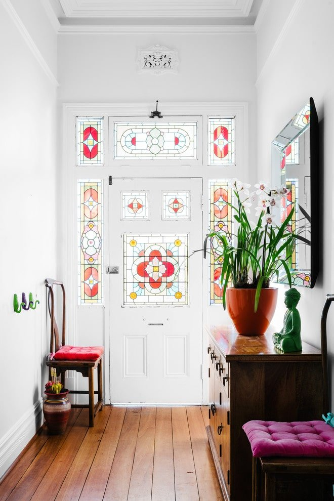 Stained glass panels surrounding the white front door bring a pop of color in this foyer with wide plank flooring and white walls adorned by a beveled mirror. It is furnished with high back chairs and a wooden console table topped with a potted plant and a small green Buddha sculpture.