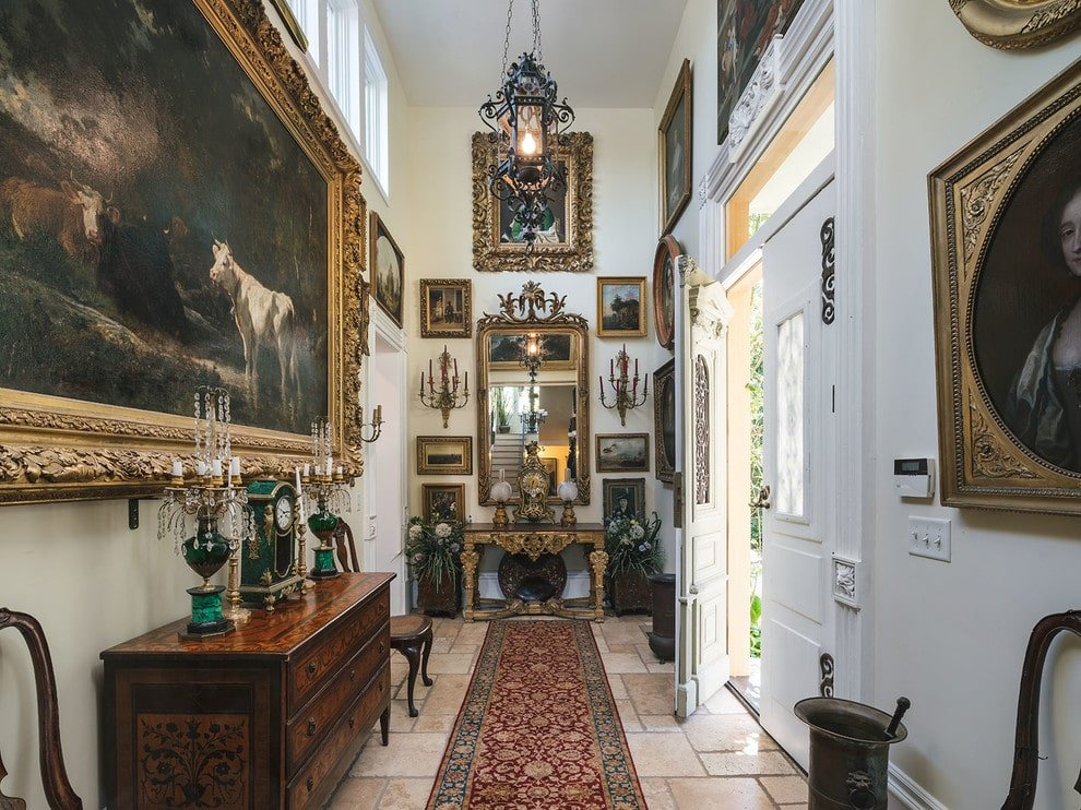 Various artworks and portraits dominate this foyer featuring a double front door and limestone flooring topped by a classic red runner. It is filled with console tables and wooden chairs lighted by an ornate glass pendant.