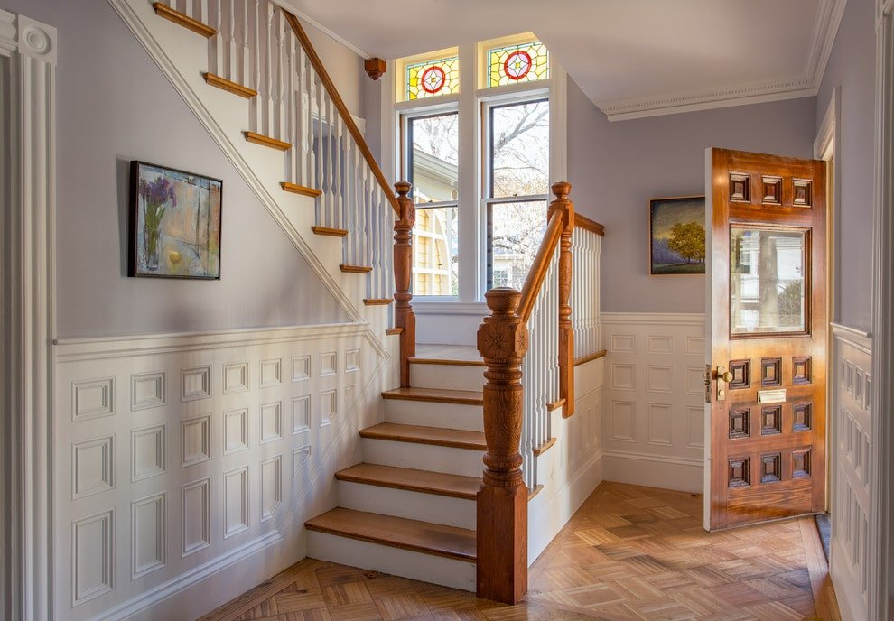 This foyer showcases a wooden front door and gorgeous artworks mounted on the soft blue walls that are clad in white wainscoting. It has glazed windows and light hardwood flooring arranged in a diamond pattern.