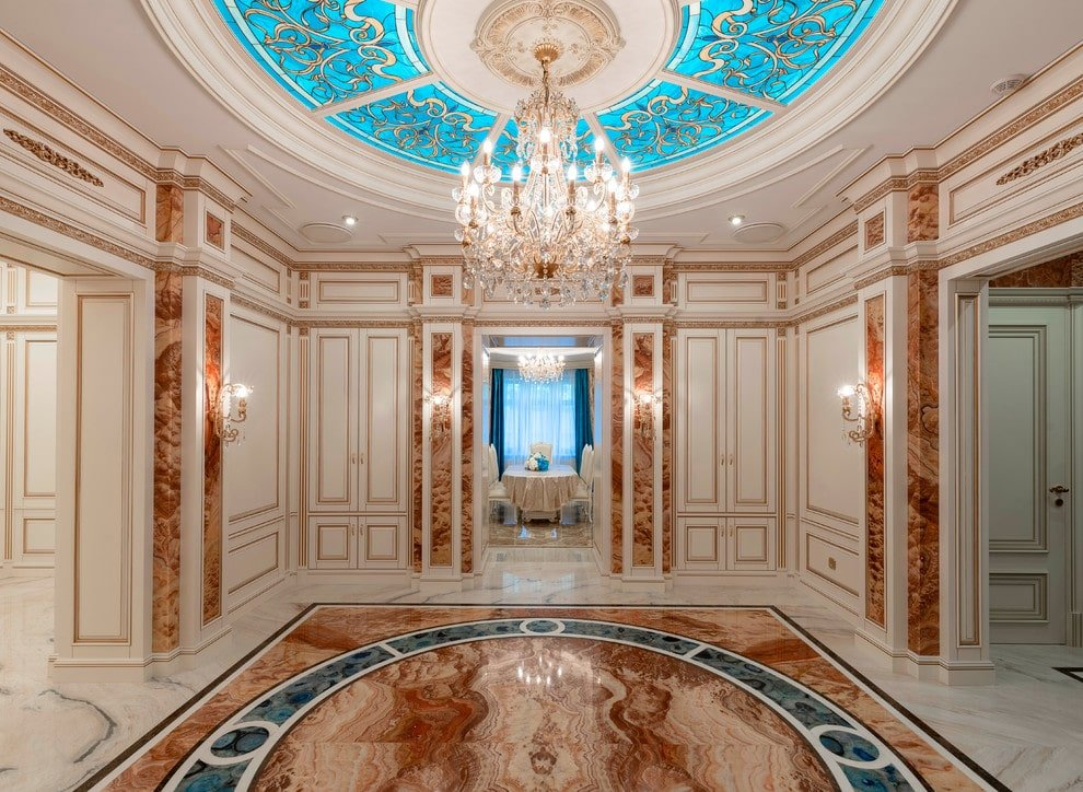 Deluxe foyer showcases a luxurious marble flooring and a stunning round tray ceiling fitted with stained glass panels. It is illuminated by a fancy crystal chandelier and matching sconces mounted on the wainscoted walls.