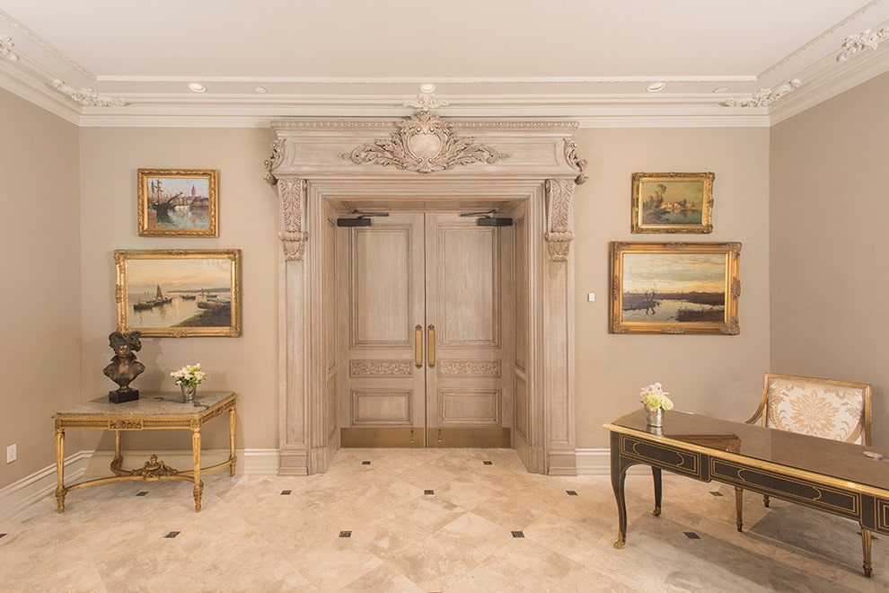 Brass framed artworks flanked a double front door that's highlighted with carved trimmings. It is accompanied by classy tables and a floral printed chair over marble tiled flooring.