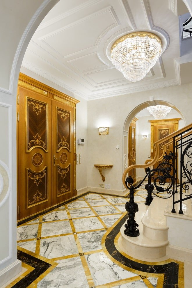 A view of the well-lit foyer through the arched doorway showcasing a gorgeous double front door and a marble staircase framed with ornate railings. It is illuminated by a beaded flush mount light fixed on the white ceiling that's lined with moldings.