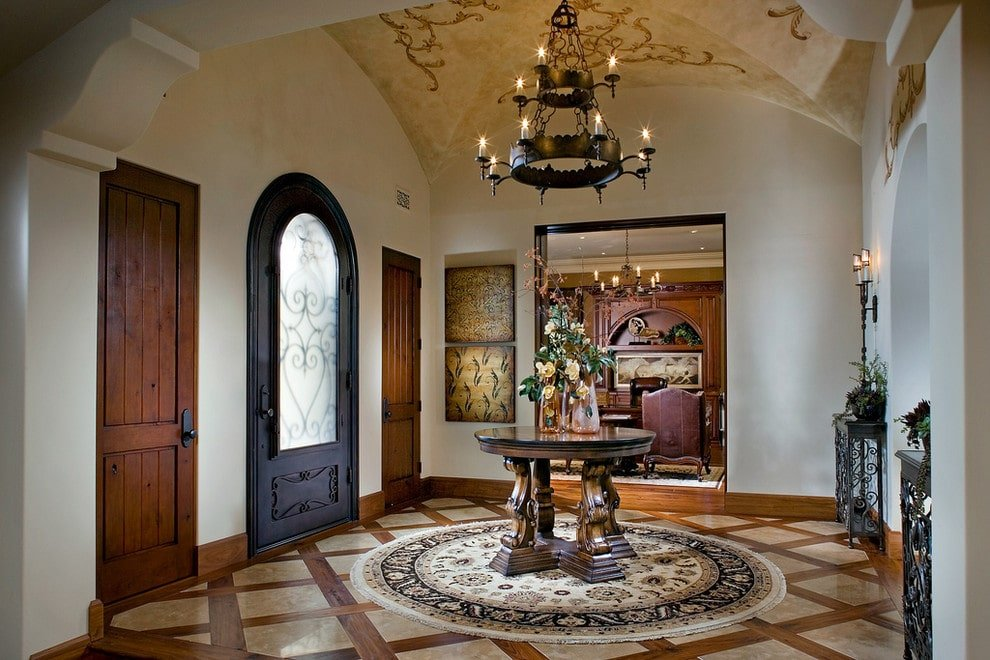 Victorian style foyer illuminated by a two-tier chandelier that hung from the groin vault ceiling. It features an arched front door and a round center table that sits on a tasseled rug over patterned flooring.