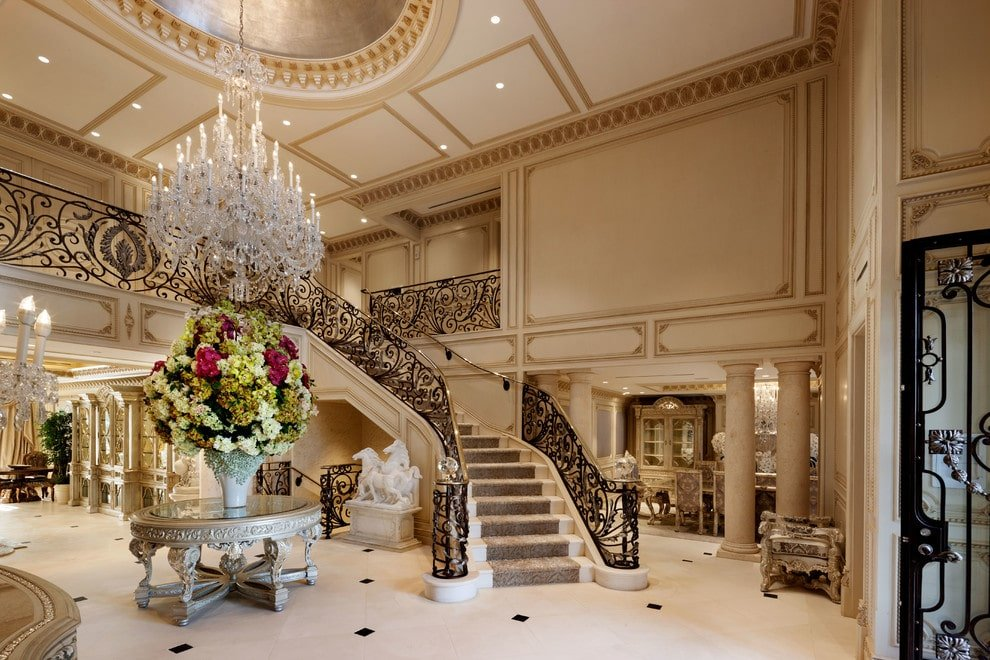 Luxury foyer illuminated by a fancy crystal chandelier that hung from the round tray ceiling. It is accented with intricate railings and a grand floral arrangement sitting on a round center table over beige tiled flooring.
