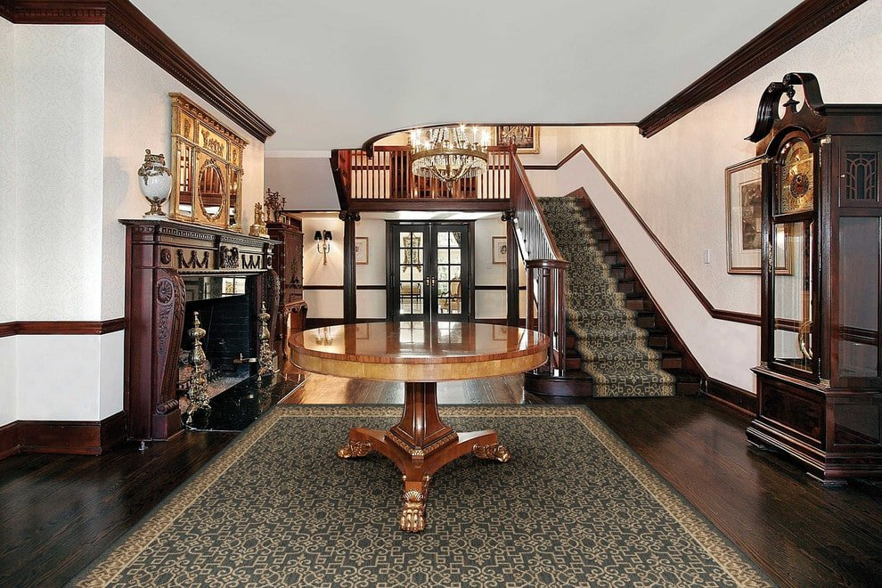 A patterned stair runner matches the bordered rug with a round center table on top. This foyer boasts a grandfather clock and a dark wood fireplace accented with a gold mirror.