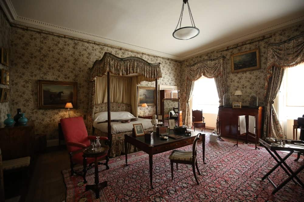 This primary bedroom has a very classic design with its floral wallpaper and a red patterned rug over the dark hardwood flooring. It offers multiple seats and a canopy bed flanked by horse artworks.