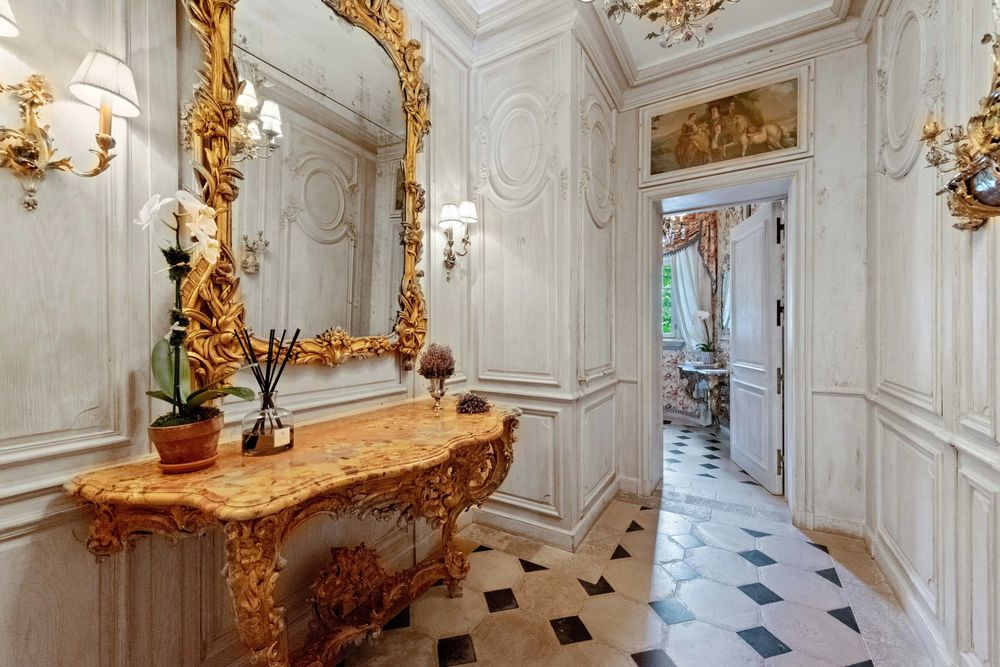 Upon entry of the mansion, you are welcomed by this foyer with patterned tiles on its floor and a built-in console table topped with a mirror with golden frames and wall-mounted sconces.
