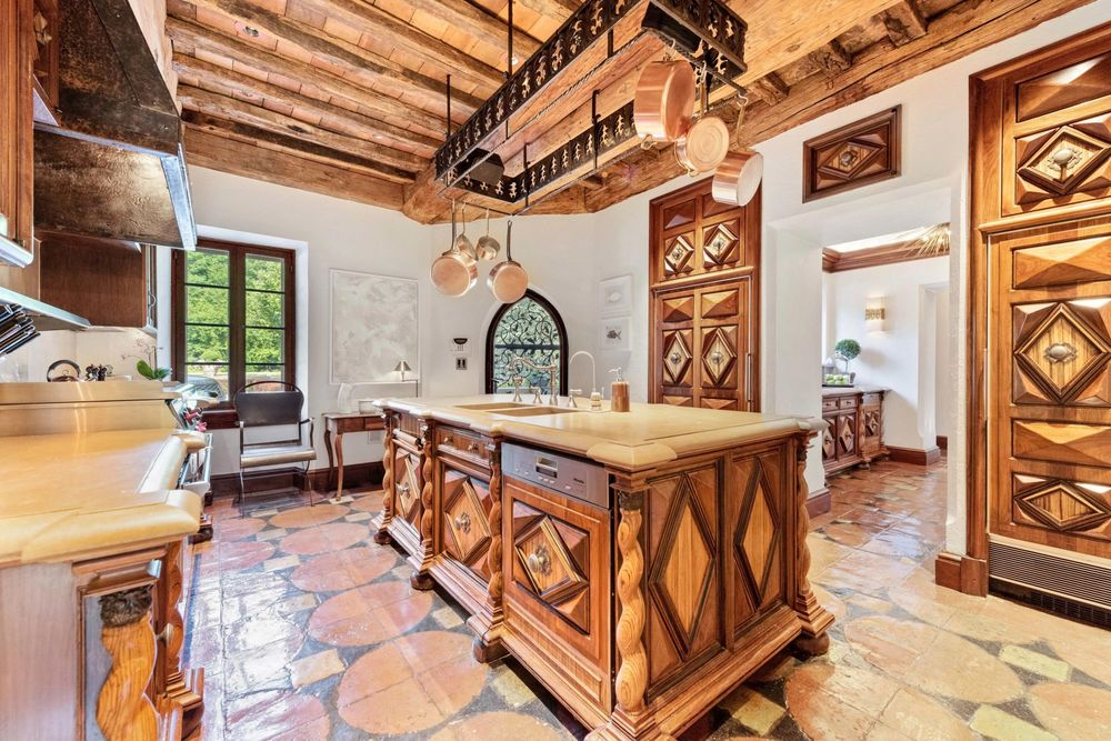 The spacious kitchen has a large wooden kitchen island in the middle topped with an iron pot rack that hangs from the wooden ceiling with exposed beams.