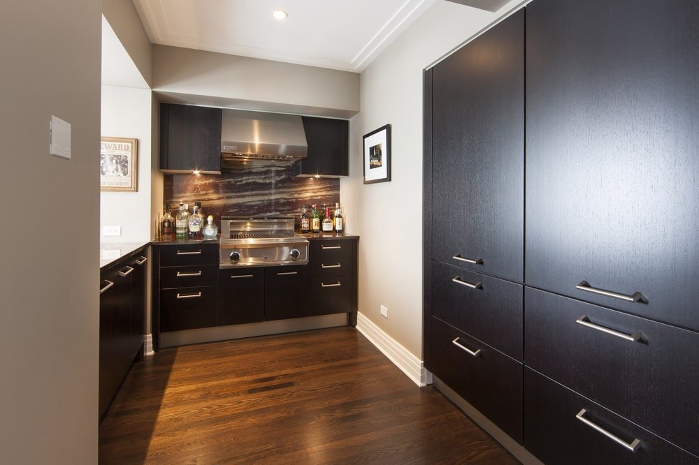 This is the kitchen with dark wooden cabinetry that blends well with the floor. These make the modern silver handles stand out along with the stainless steel cooking area.