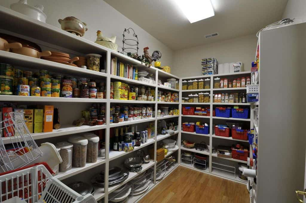 This is a simple walk-in kitchen pantry with its walls filled with light gray shelves for food storage. There are also brightly-colored baskets baskets within the shelves that stand out along with the decors at the top shelf serve as adornment to the small room.