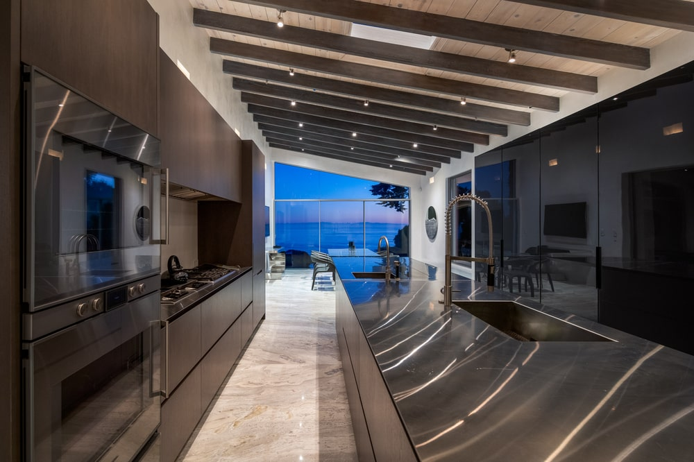 This is a close look at the kitchen with dark brown tones and dark modern appliances that match the exposed beams.