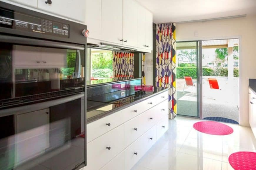 This is the kitchen with bright white kitchen cabinets to match the white floor and ceiling. These make the stainless steel appliances stand out along with the colorful curtains and area rug.