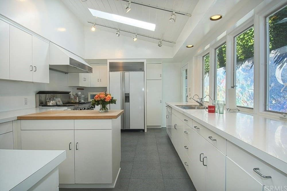 Kitchen featuring black tiles flooring and a custom ceiling with a skylight, along with glass windows and track ceiling lights.