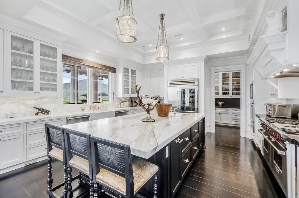 This is a close look at the kitchen that has a large kitchen island with dark cabinetry that contrasts the marble countertop and matches the dark hardwood flooring.