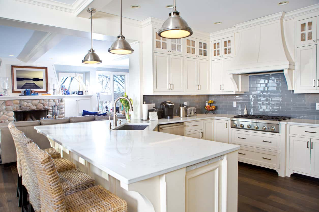 U-shaped kitchen with peninsula breakfast bar and white cabinetry.