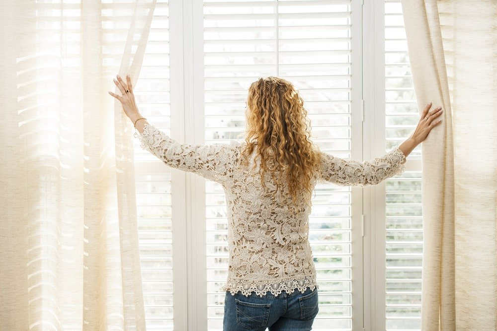 Back view of a woman opening the window with shades and blinds.