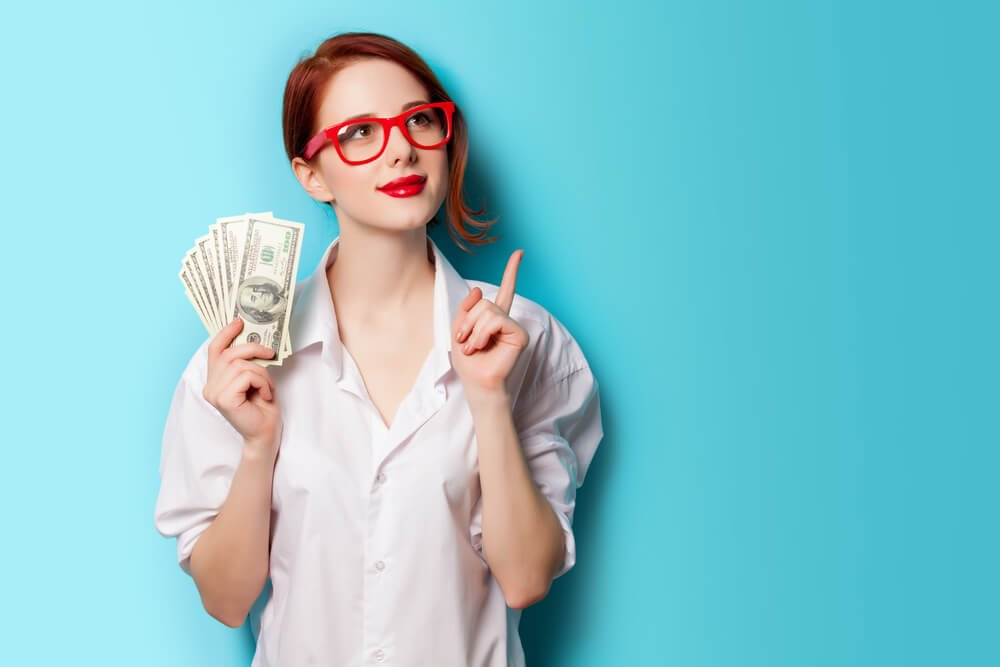 Woman wearing red glasses and holding some dollar bills.