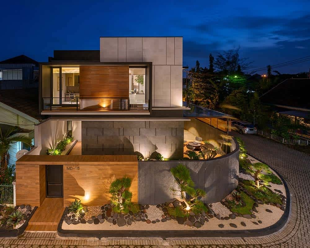 This is an aerial view of the house exterior showcasing the landscaping that has a Zen garden lining the outer walls of the house with outdoor lighting that matches the windows of the house.