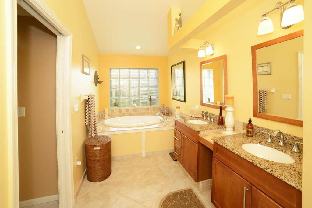 Primary bathroom with yellow walls and a shed ceiling, along with tiles flooring. It offers a drop-in tub on the side along with a walk-in shower and two sink counters with marble countertops.