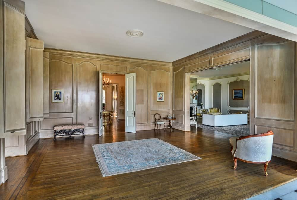 A spacious entry hall featuring elegant brown walls and hardwood flooring along with a regular white ceiling.