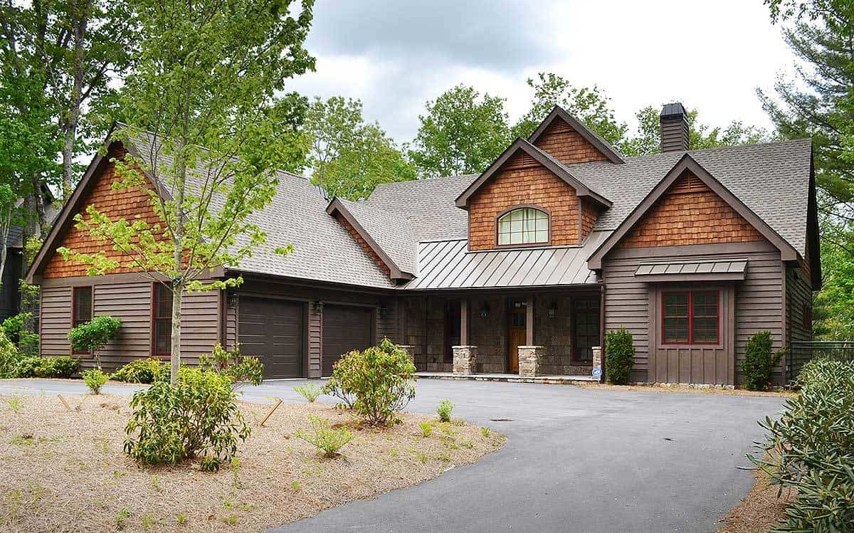 The asphalt driveway in front of this charming home is flanked by gorgeous landscaping of shrubs and trees that give color to the earthy exterior walls of the house.