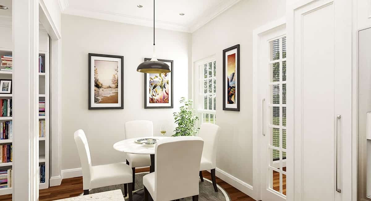 This is a bright white informal dining area just beside the shelves of the living room. It has a matching white dining set complemented by the potted plant and the wall artworks.