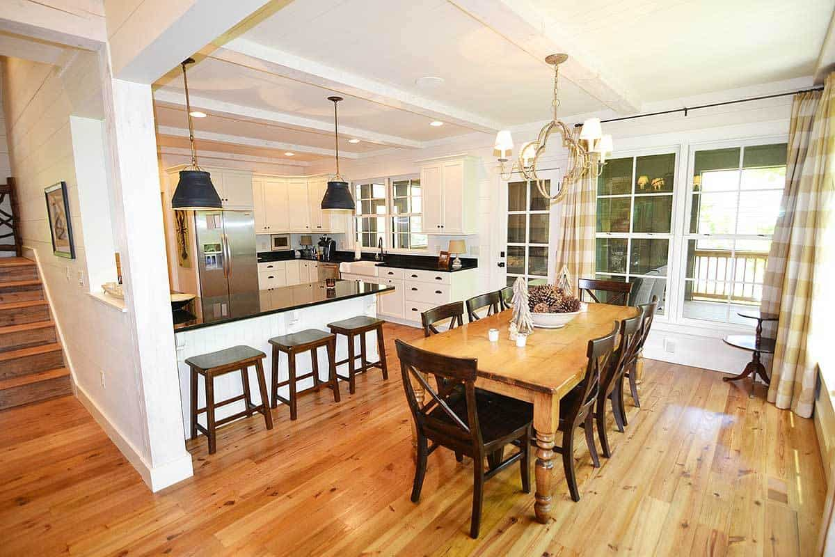 This is an informal dining area beside the kitchen that has a large wooden dining table to match the hardwood flooring. The wooden chairs surrounding it are of a slightly darker hue to contrast the white walls and ceiling that hangs a simple chandelier over the table.