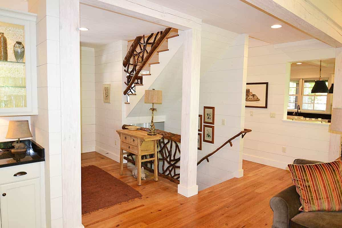 The small foyer right beside the living room has a small wooden console table with a table lamp and a clear view of the staircase to the upper and lower levels of the house.