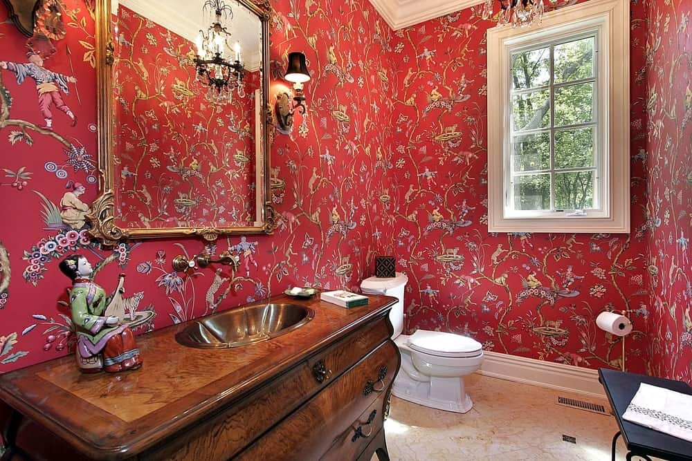 A beautiful powder room complemented by its floral red wallpaper that makes the white details stand out.