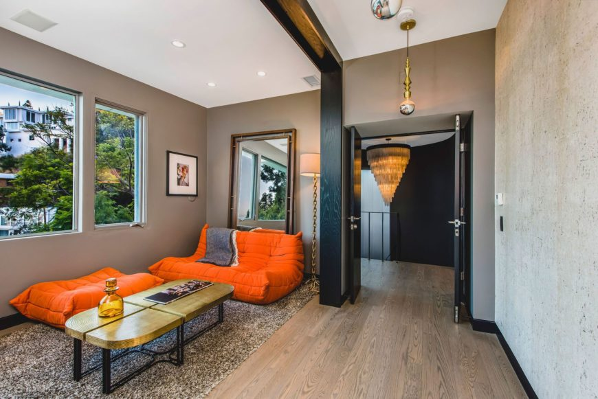 A look at the small living space with orange seats. The area features hardwood flooring and gray walls. Images courtesy of Toptenrealestatedeals.com.