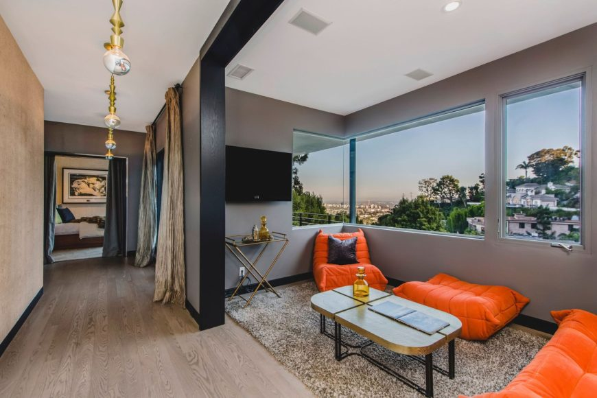 A small living space featuring a set of orange seat and a flat-screen TV on the wall, set near the glass windows. Images courtesy of Toptenrealestatedeals.com.