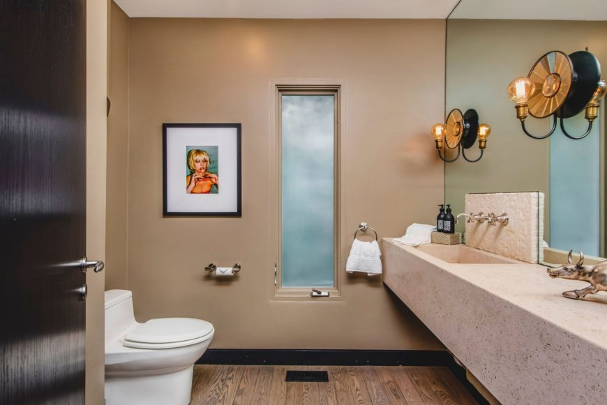 A toilet area featuring hardwood flooring and beige walls. The room also offers a floating vanity with a single sink. Images courtesy of Toptenrealestatedeals.com.